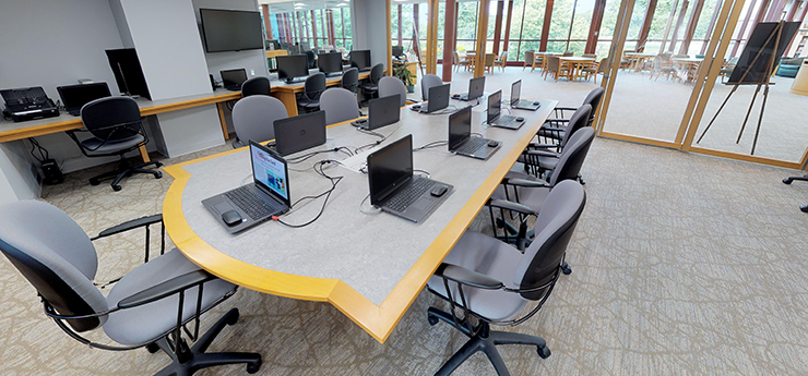 Technology center with long conference table and laptops in front of each chair