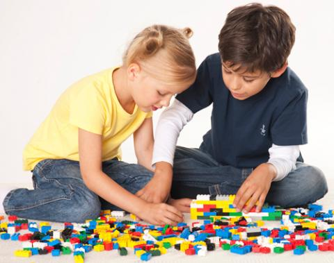 Two children playing with Legos